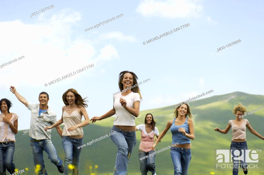 Stock Photo: Group of friends running through mountain field front view.