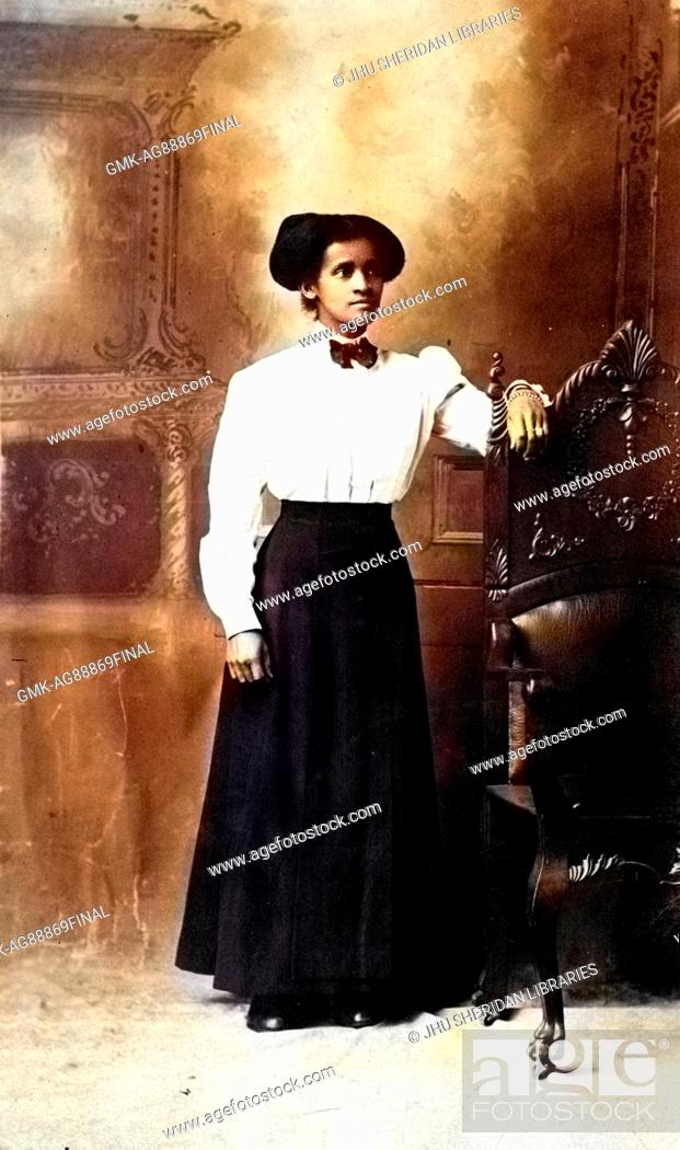 Imagen: Full-length portrait of an African American woman standing in front of a decorative mural, she is resting one are on a high wooden back of a chair.