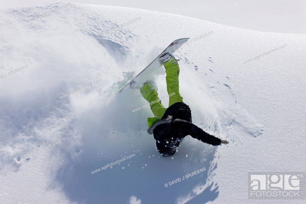Stock Photo: A snowboarder tumbles over in deep fresh powder snow.