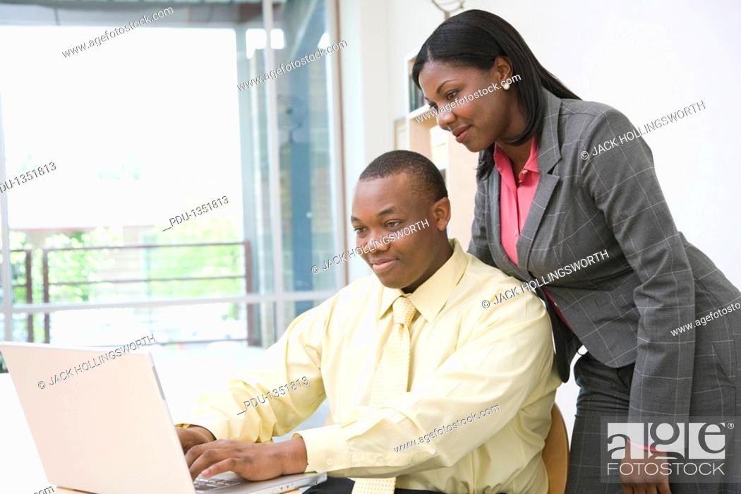 Stock Photo: Business man and woman working at desk in office, side view.