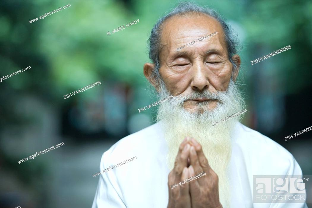 Stock Photo: Elderly man in traditional Chinese clothing, hands clasped in prayer.