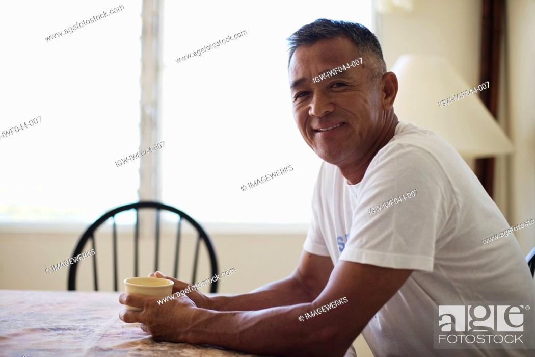 Stock Photo: Mature man holding cup smiling.