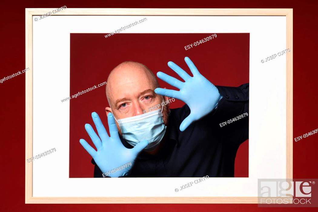 Stock Photo: picture of man with gloves and mask with open hands on a red background.