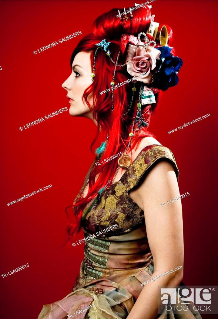 Stock Photo: The profile of young woman with decorations in her red hair.