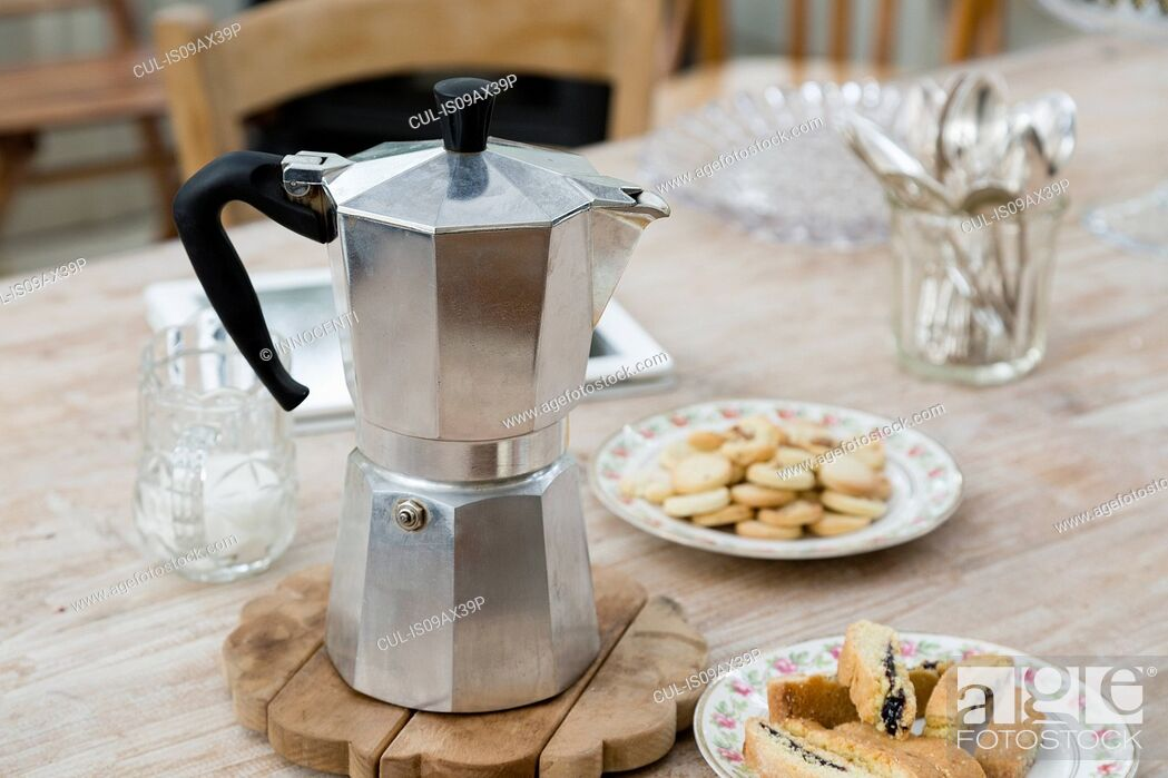 Stock Photo: Stove top coffee pot with plates of baked good on dining table.