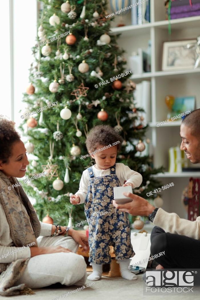 Imagen: Couple helping baby daughter open Christmas gift in living room.