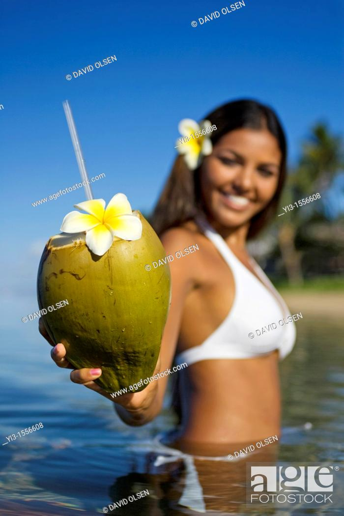 Stock Photo: Smiling, attractive local girl holds out a coconut with straw and flower ready to drink at Lahaina, Maui, Hawaii.