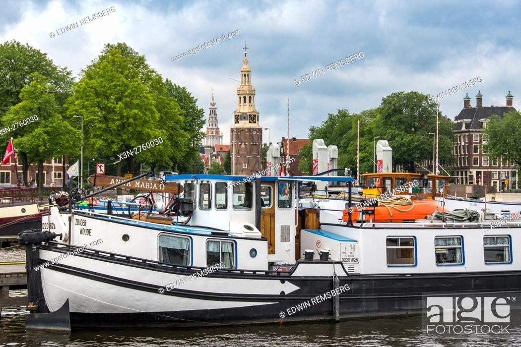 Stock Photo: Amsterdam, Netherlands waterfront view of a boat docked in the harbor. In the background is the famous Montelbaanstoren Tower and other historical architecture.