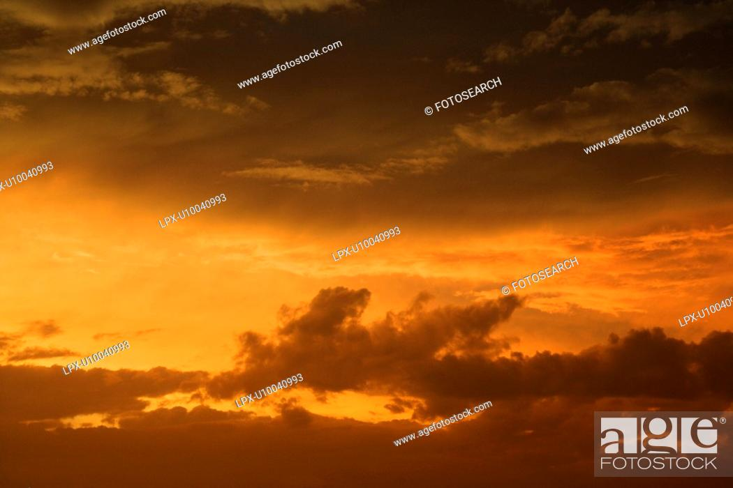 Stock Photo: Golden yellow and orange sunset sky and clouds.