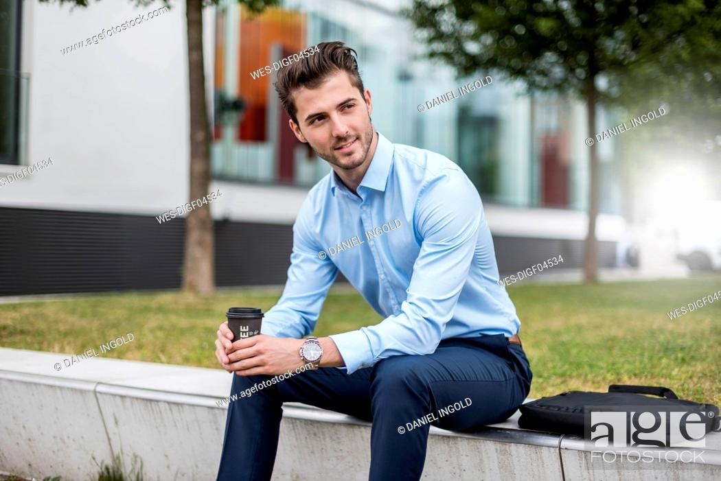 Stock Photo: Smiling businessman sitting outdoors with takeaway coffee.