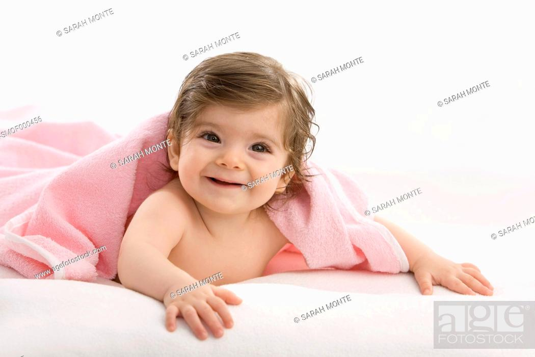 Stock Photo: Baby girl with pink blanket, smiling.
