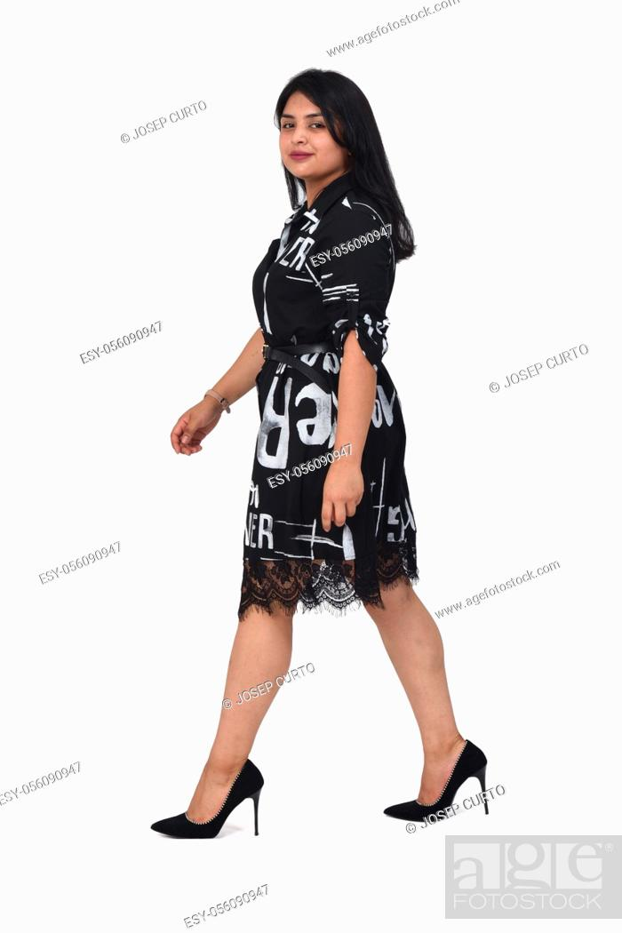 Stock Photo: sideways of latin woman with dress and high heels walking on white background, looking at camera.