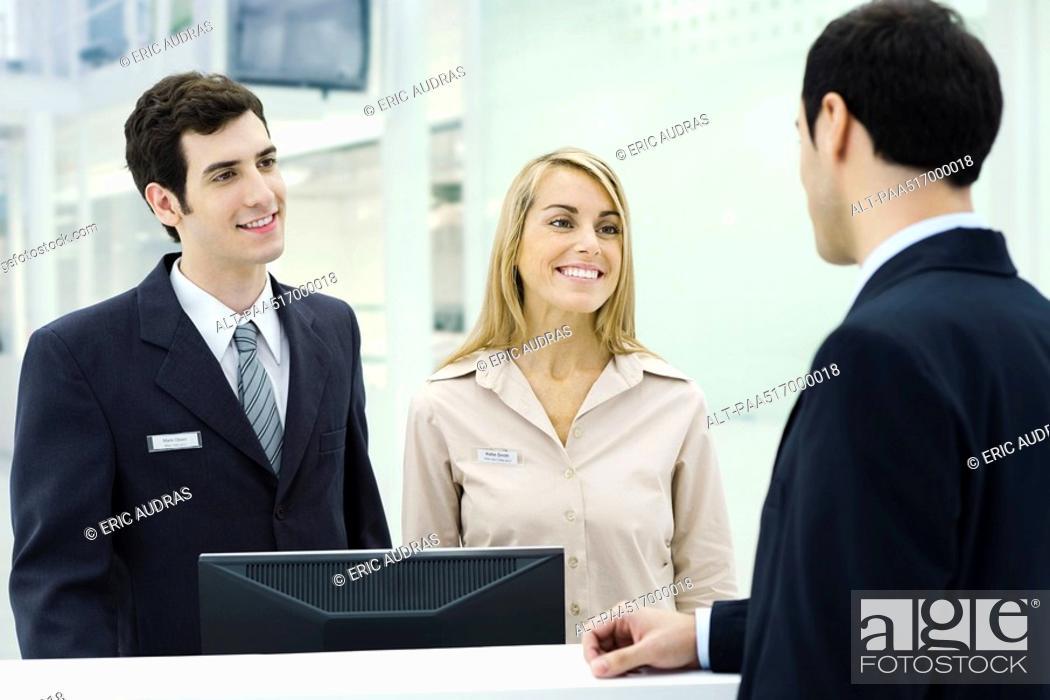 Stock Photo: Customer service representatives smiling at businessman waiting at counter.