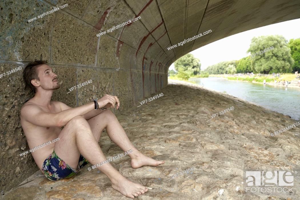 Stock Photo: man sitting under bridge Wittelsbacherbrücke at river Isar, in Munich, Germany.