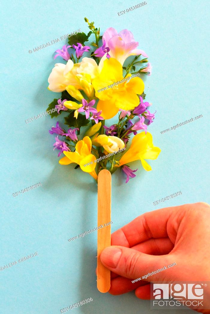 Stock Photo: Concept hand holding popsicle from spring flowers.