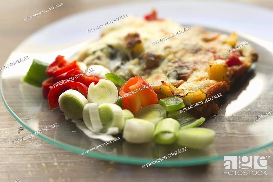 Photo de stock: Vegetable lasagna in a glass dish on a wooden background.