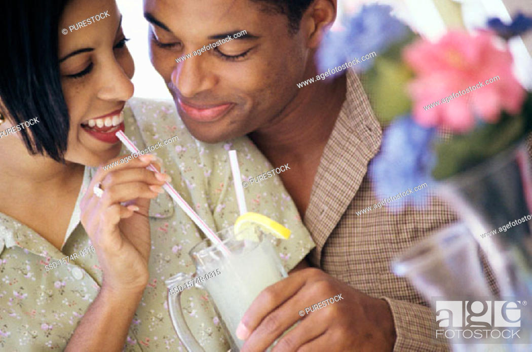 Stock Photo: Young couple sharing a drink.