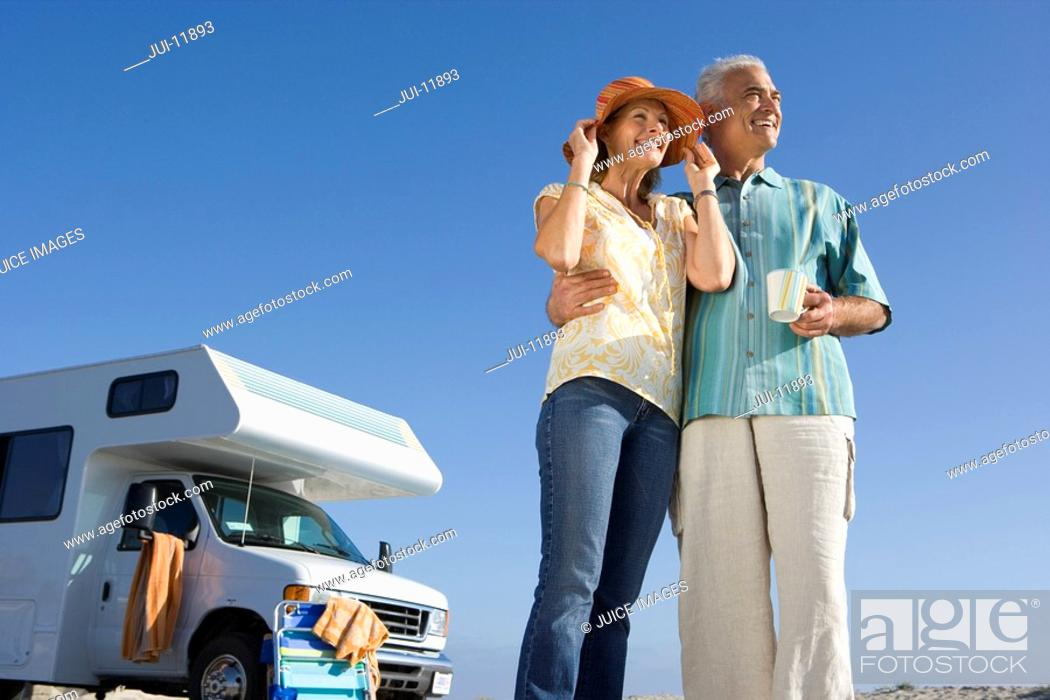 Stock Photo: Mature couple by motor home on beach, man with mug, woman with hands on hat, low angle view.
