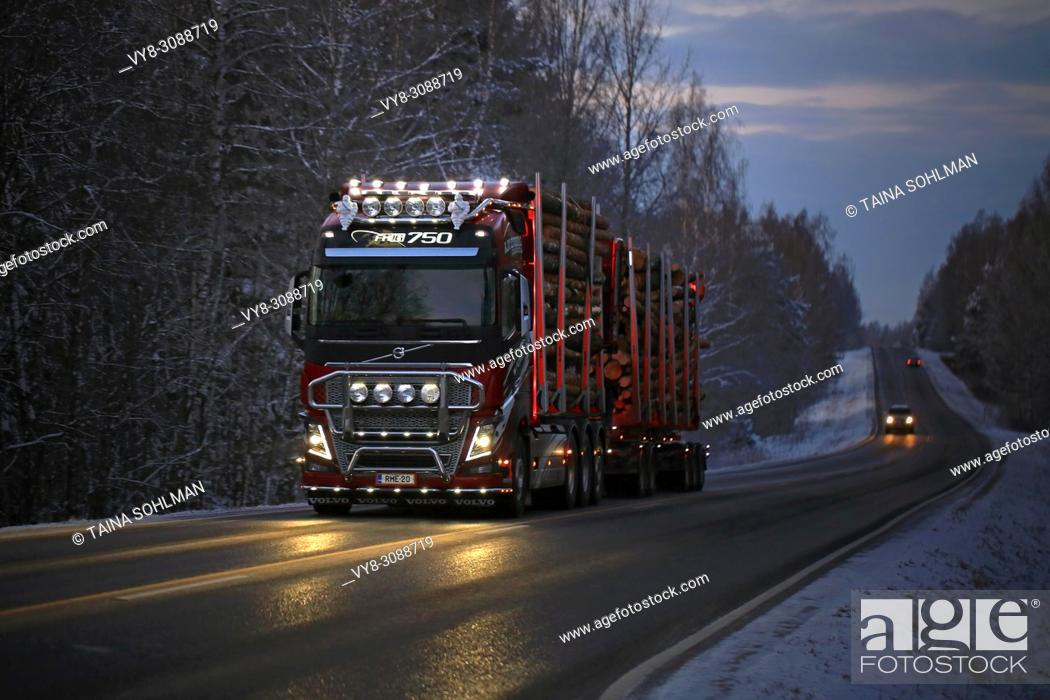 Stock Photo: Customized Volvo FH16 750 logging truck of R. M. Enberg Transport Ab lights up the road as it hauls log load through rural landscape on a dark winter evening.