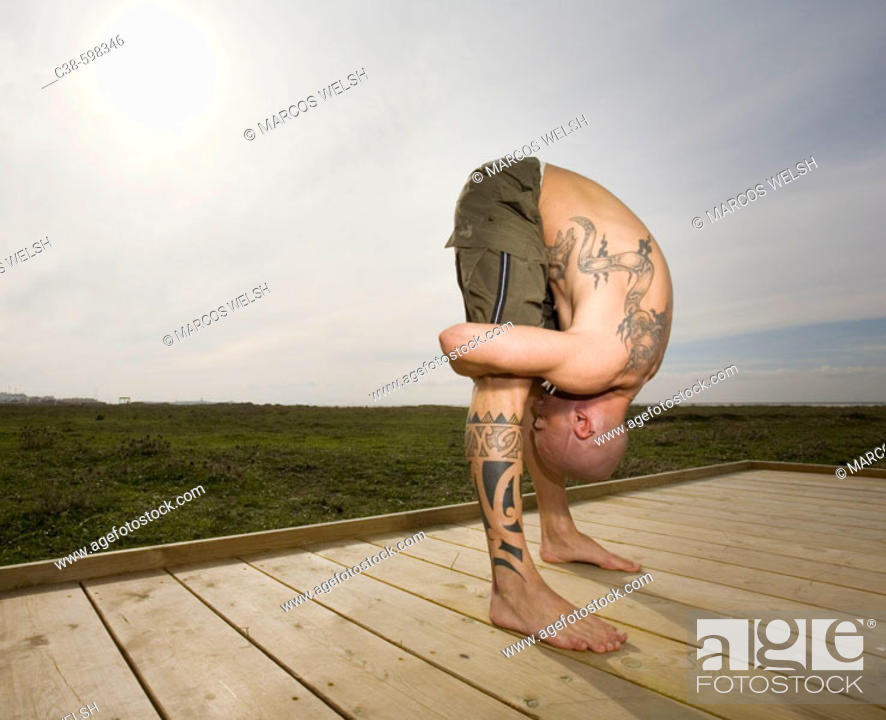 Stock Photo: Man Stretching on a Wooden Platform.