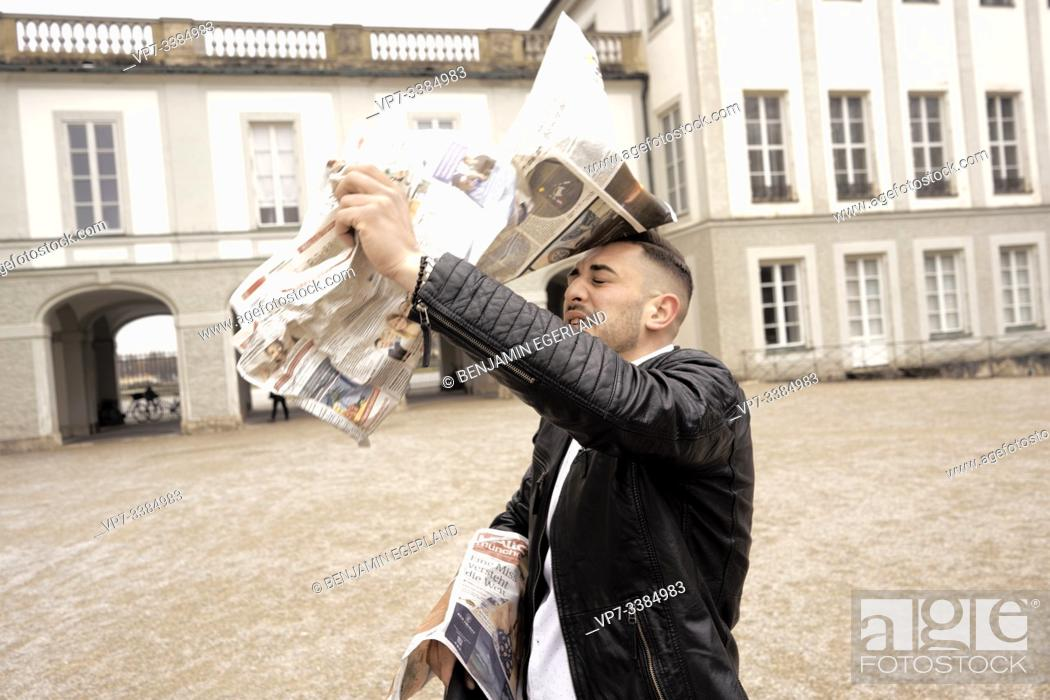 Stock Photo: Man assailed by flying newspapers, in Munich, Germany.