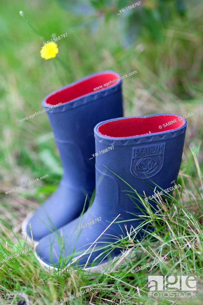 Stock Photo: Blue rain boots of a child placed in the grass.