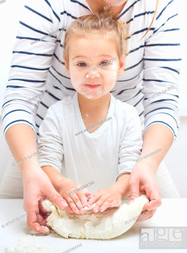 Stock Photo: Cute little girl with her mother kneading dough at home.