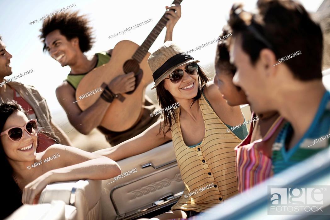 Imagen: A group of friends in a pale blue convertible on the open road, driving across a dry flat plain surrounded by mountains.