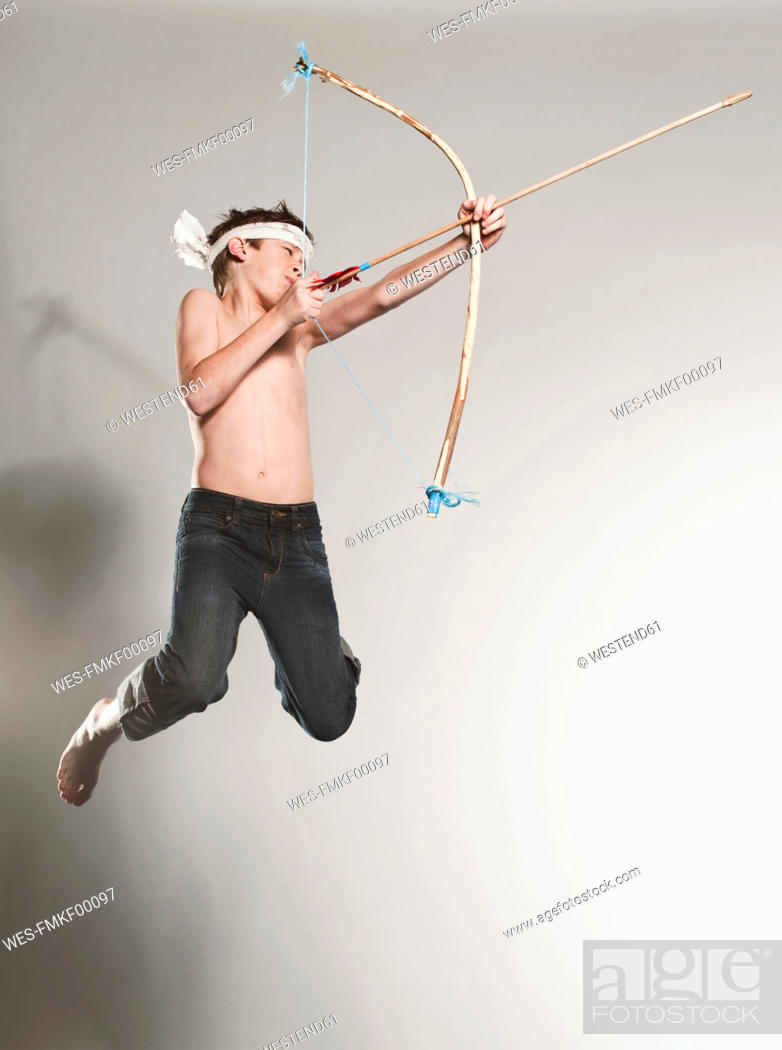 Stock Photo: Boy 12-13 jumping with holding bow and arrow.
