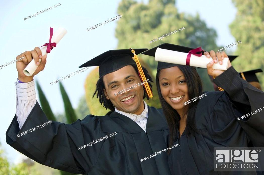 Stock Photo: Two graduates hoisting diplomas outside portrait.
