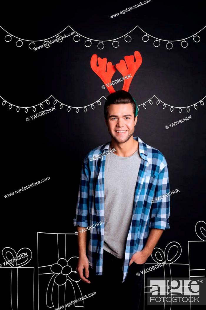 Stock Photo: Holiday mood. Joyful relaxed young man smiling and wearing Christmas reindeer antlers while standing near presents against isolated black background.