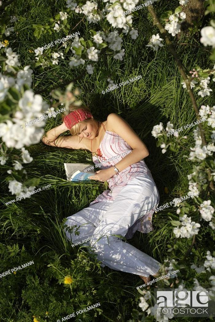 Stock Photo: Lies woman, young, blond, spring, meadow, book, reads, tree, blooms, detail, from above, 20-30 years, summerwear, hairband, garden, fruit tree, blooms.