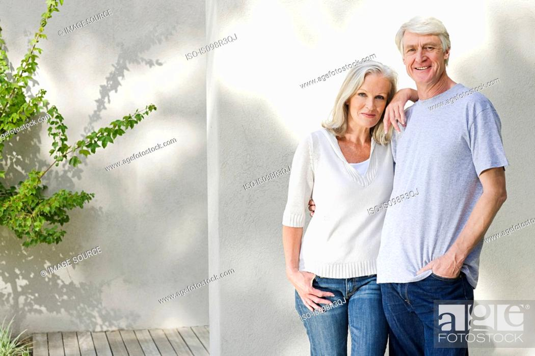 Stock Photo: Middle aged couple standing outside on deck.