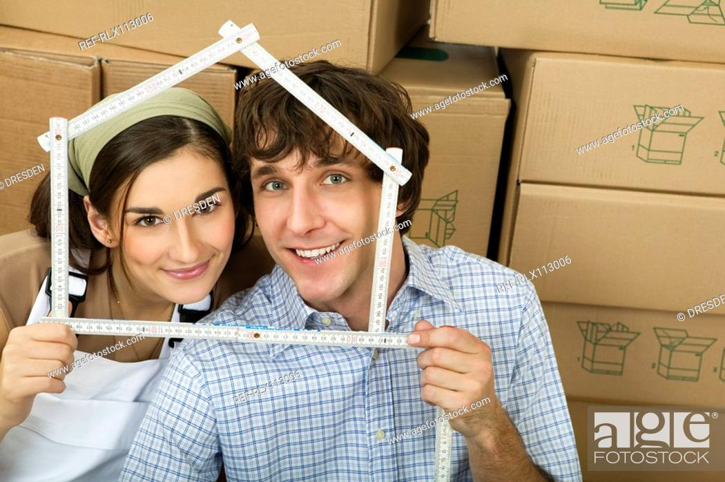 Stock Photo: Couple holding ruler in shape of house.