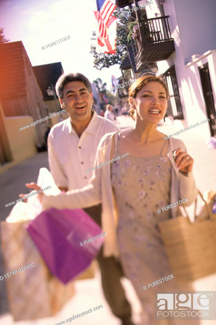 Stock Photo: Young couple walking with shopping bags.