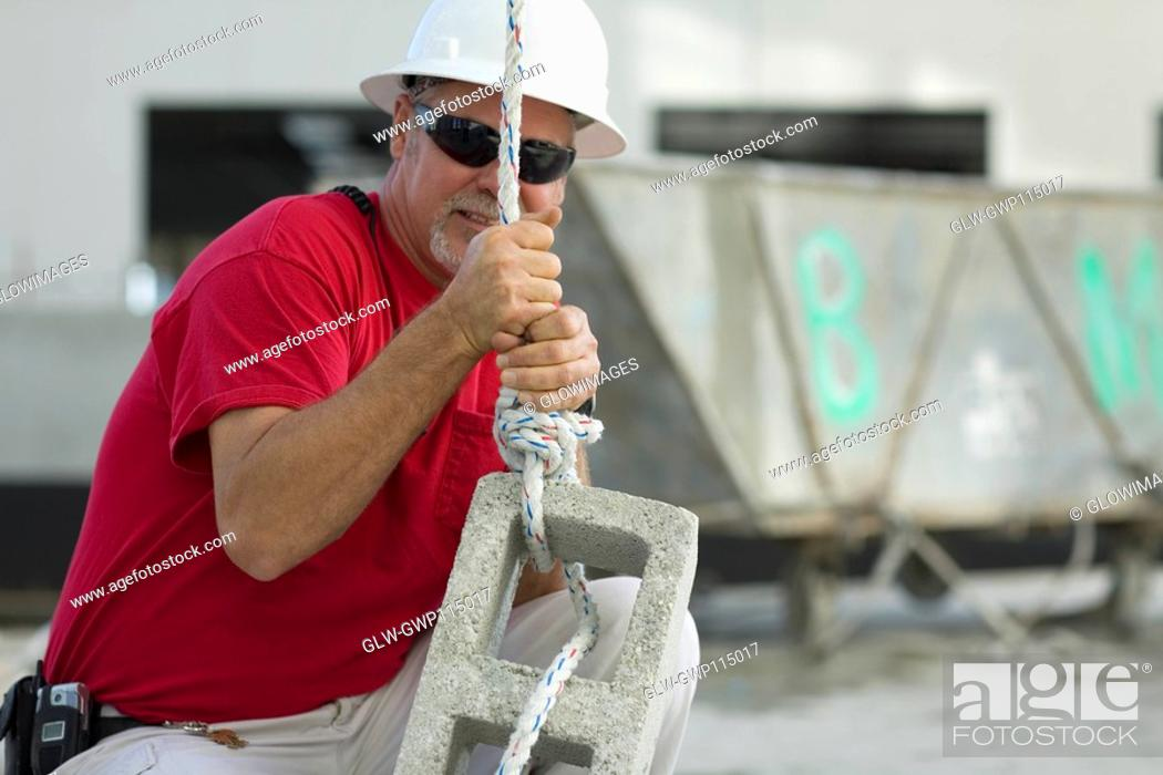 Stock Photo: Male construction worker tightening a rope on a concrete block.