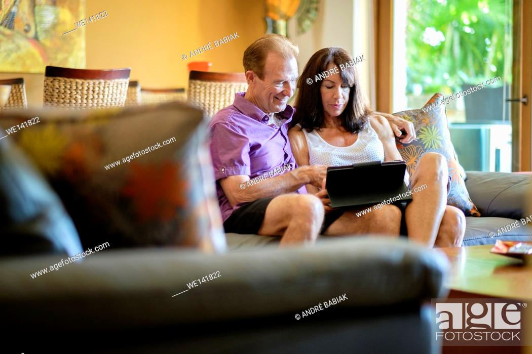 Stock Photo: Senior man and woman sitting on the couch in the livingroom of their upscale home using a tablet computer.