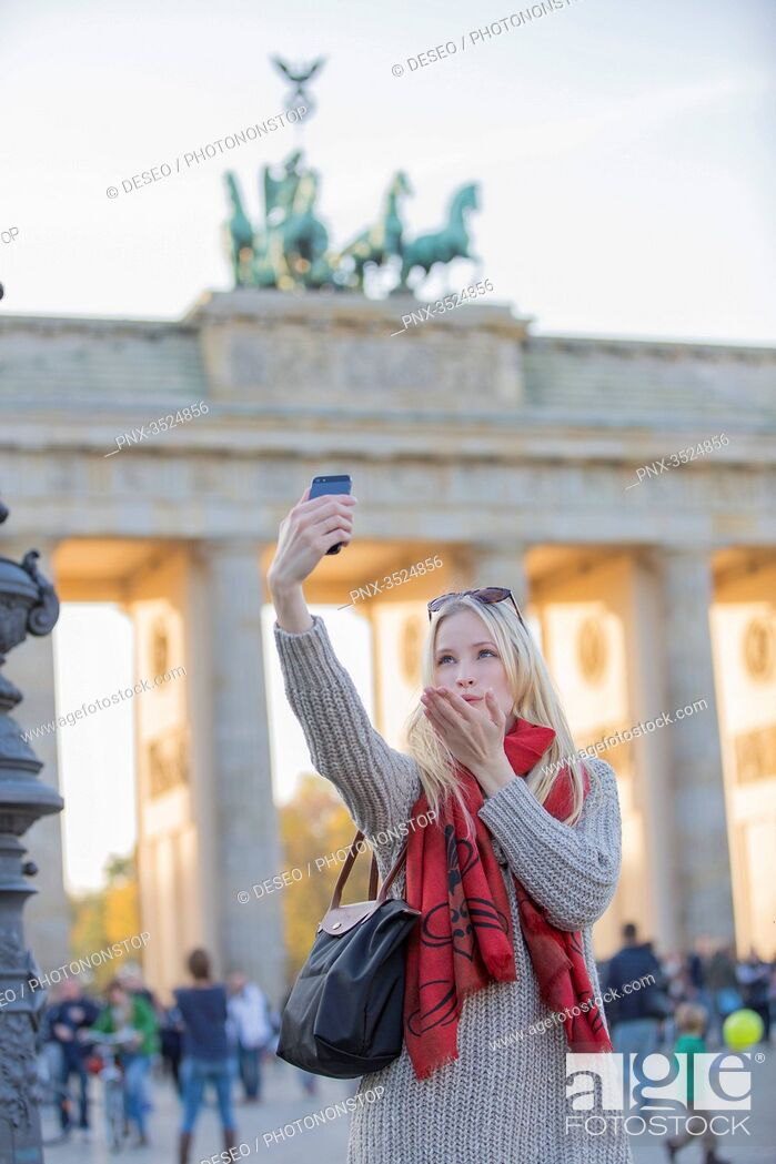 Imagen: Pretty blonde woman doing a selfie and sending a kiss in front of the Brandenburg Gate in Berlin, Germany.
