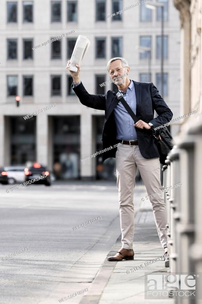 Stock Photo: Grey-haired businessman with newspaper calling a taxi in the city.