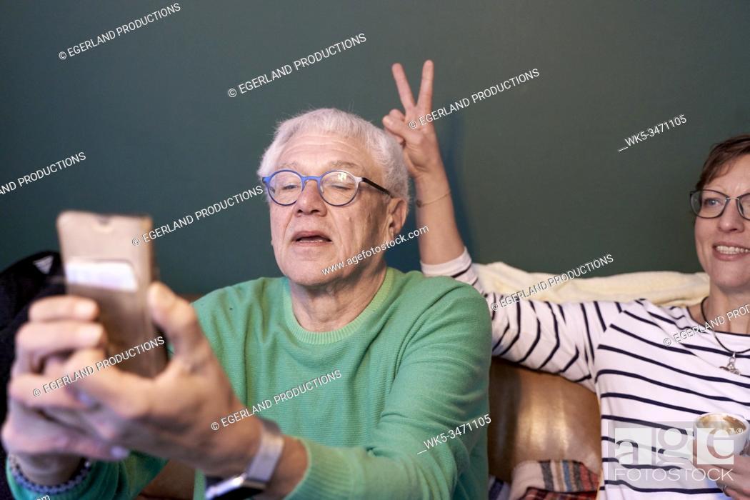 Imagen: Senior man looks at his phone while woman makes V-sign behind him.