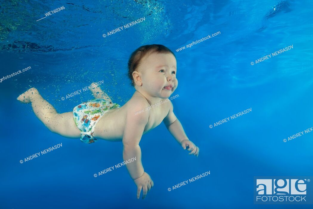 Stock Photo: little boy learns to swim underwater in the pool.