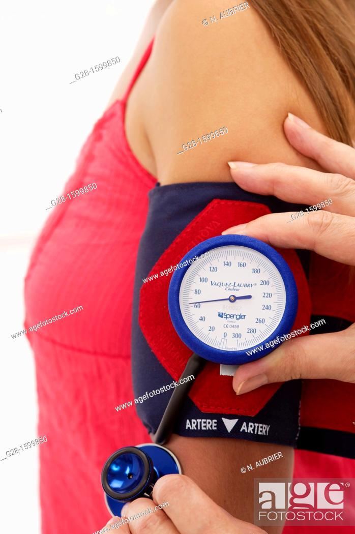 Stock Photo: Young woman undergoing a blood pressure test with a blood pressure gage, no head, cropped picture.