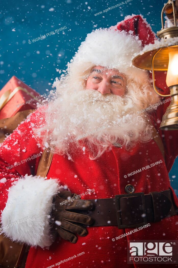 Stock Photo: Photo of happy Santa Claus outdoors in snowfall lights the way with vintage lantern while carrying gifts to children.