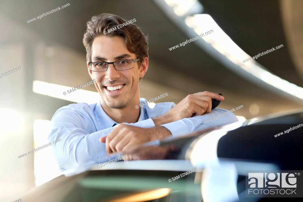 Stock Photo: Portrait of smiling businessman leaning on car.