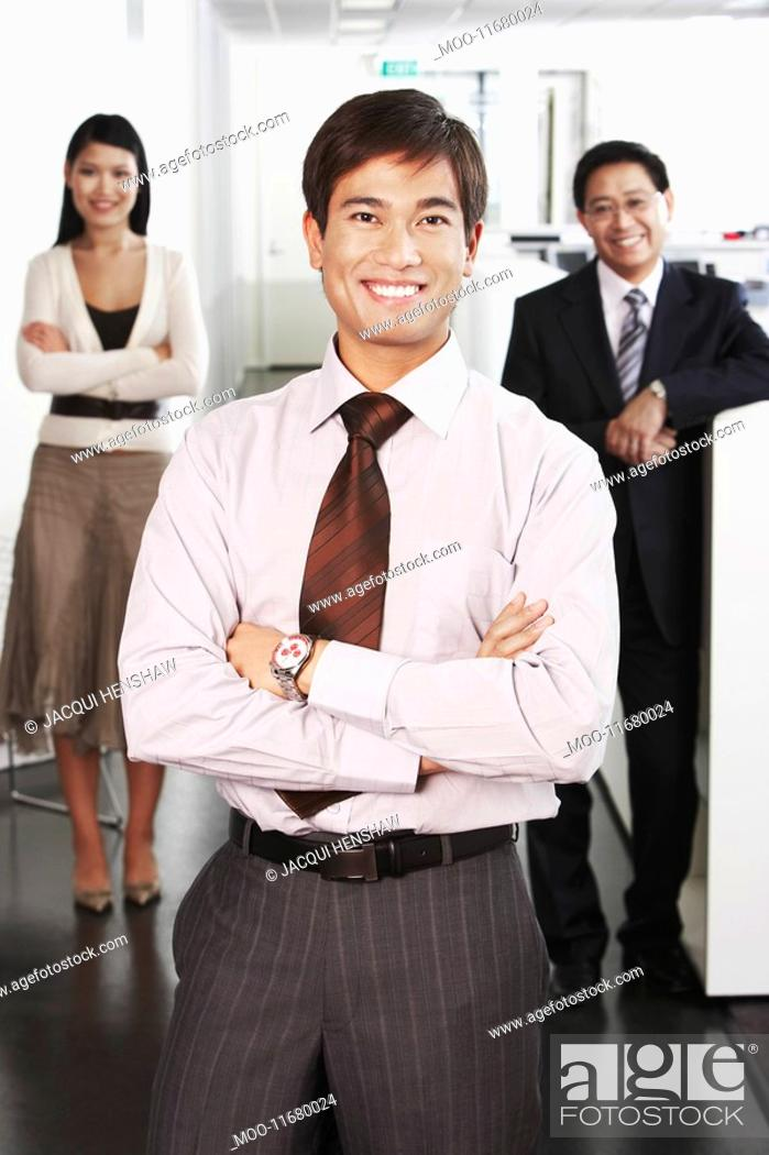 Stock Photo: Business man standing in front of colleagues in office portrait.