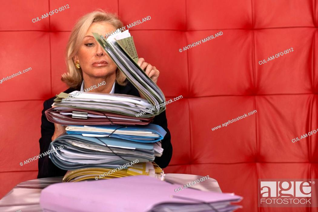 Stock Photo: Businesswoman working at a table with red seating.