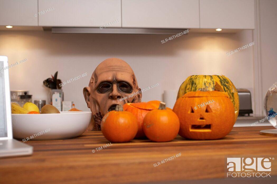 Stock Photo: Jack-o-lanterns and mask in kitchen.