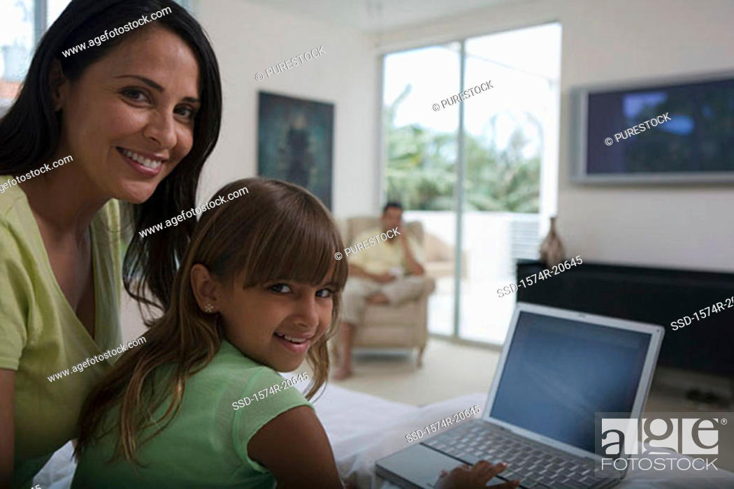 Stock Photo: Portrait of a girl using a laptop with her mother sitting behind her.