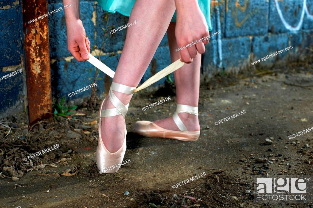 Imagen: Ballet dancer tying ribbon on ballet shoe.