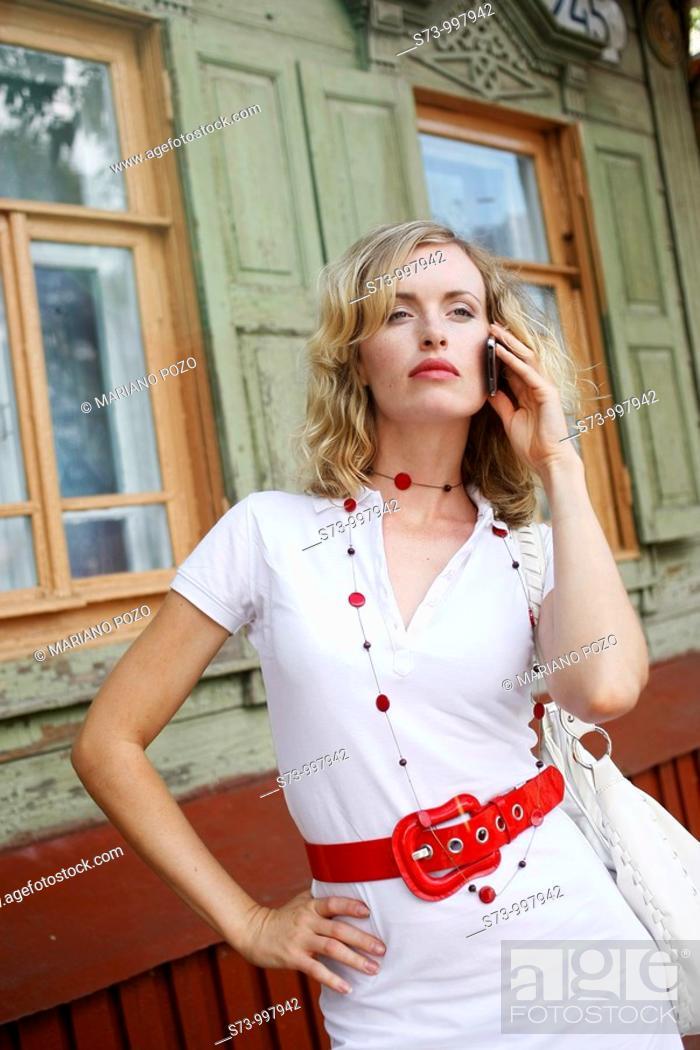 Stock Photo: Businesswoman using cell phone in Samara street, Samara region, Russian Federation, Russia.